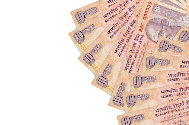 10インドルピーの請求書はコピースペースのある白い壁に隔離されています。豊かな生活の概念的な壁。大量の自国通貨の富