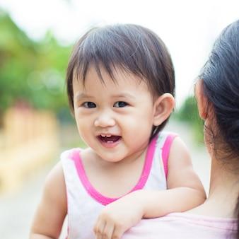 10 месяцев милый ребенок чувствует себя счастливым и улыбается с матерью в саду