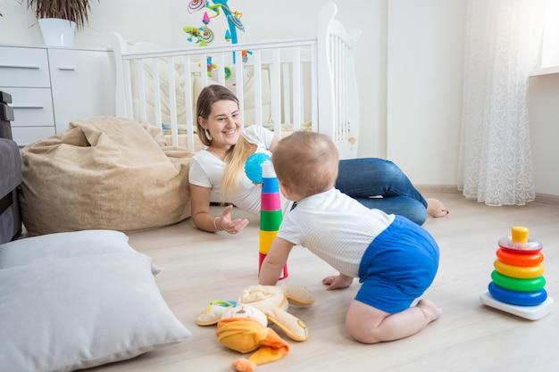 リビングルームの床で這って楽しんでいる生後10ヶ月の男の子