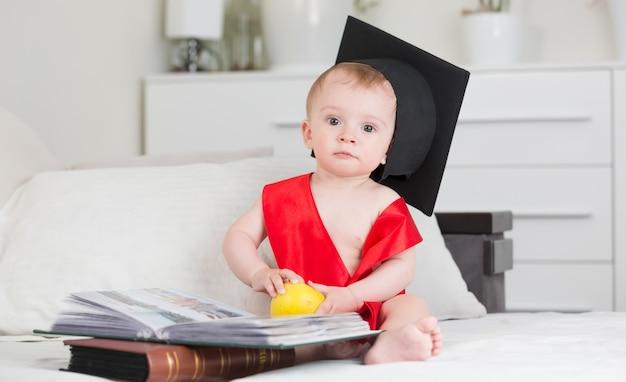 책과 함께 소파에 앉아 졸업 모자에 10 개월 된 아기