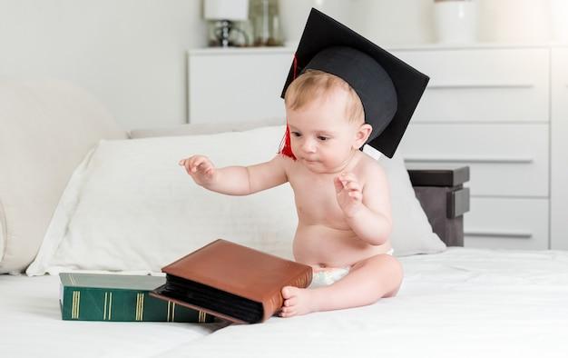大きな本と一緒に座っている鏝板の帽子をかぶった生後10ヶ月の男の子