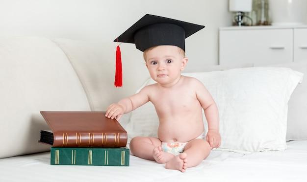 本のスタックと座って鏝板の帽子をかぶった生後10ヶ月の男の子