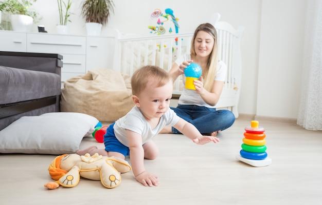 10-месячный мальчик играет на полу с красочными игрушками