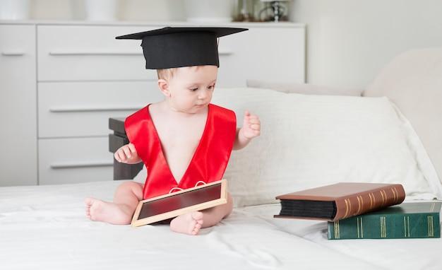 10-месячный мальчик с книгами в выпускной шапке