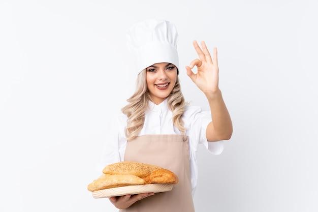 シェフの制服を着た10代女性。指でokサインを示す分離白でいくつかのパンとテーブルを保持している女性のパン屋