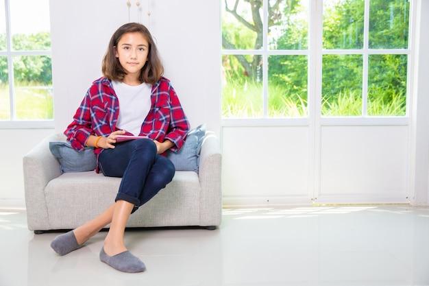 白人の10代の少女が自宅のソファーでスマートフォンやタブレットpcをプレイ