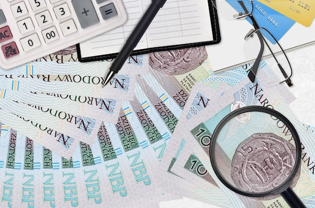 Купюры 10 польских злотых и калькулятор с очками и ручкой. концепция сезона уплаты налогов или инвестиционные решения. ищу работу с высокой зарплатой