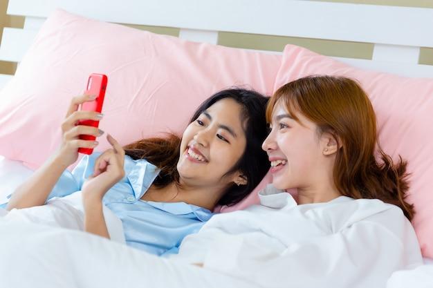 陽気な10代女性がベッドでスマートフォンselfieを使用します。