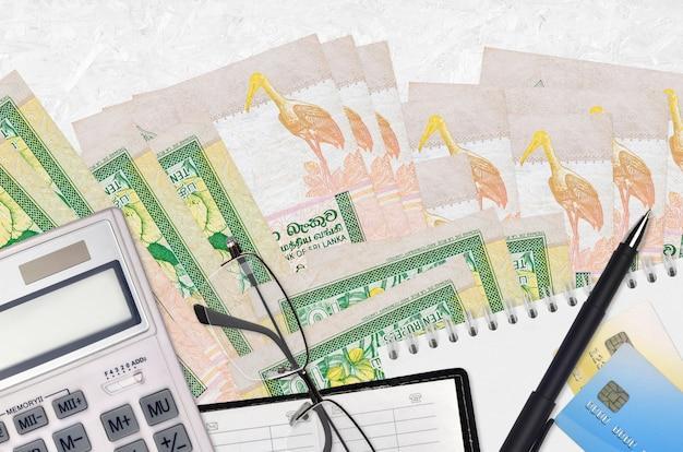 Купюры 10 шри-ланкийских рупий и калькулятор с очками и ручкой. концепция уплаты налогов или инвестиционные решения. финансовое планирование или бухгалтерские документы