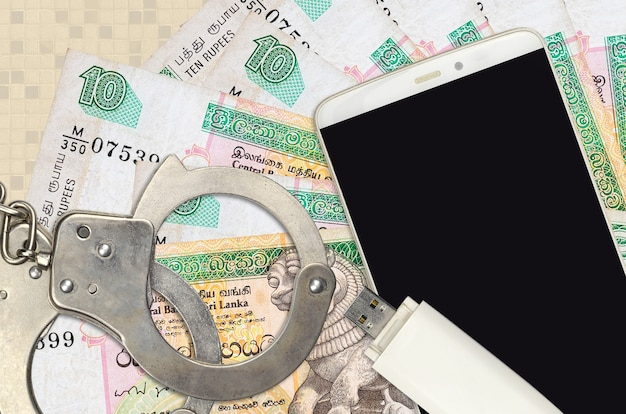 10 sri lankan rupees bills and smartphone with police handcuffs