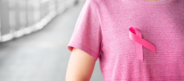 10月の乳がん啓発月間、人々の生活と病気をサポートするためのピンクのリボンが付いたピンクのtシャツの女性。医療、国際女性の日、世界がんの日コンセプト