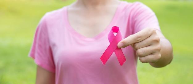 10月乳がん啓発月間、ピンクのtシャツを着た大人の女性。ピンクのリボンを手に持って、人々の生活と病気をサポートしています。国際女性、母および世界のがんの日のコンセプト