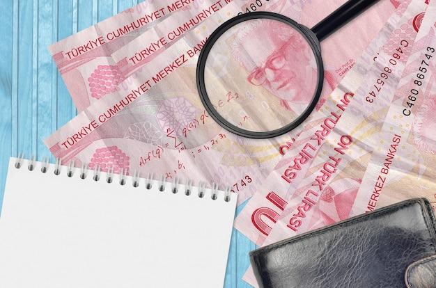 터키 리라 지폐 10 개와 검은 색 지갑과 메모장이있는 돋보기
