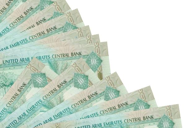 Счета 10 дирхамов оаэ лежат изолированно на белой стене с копией пространства, сложенными в веер крупным планом. понятие времени выплаты жалованья или финансовые операции