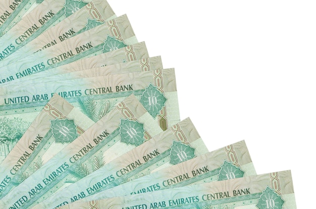 10 uae dirhams bills lies isolated on white wall with copy space stacked in fan close up. payday time concept or financial operations