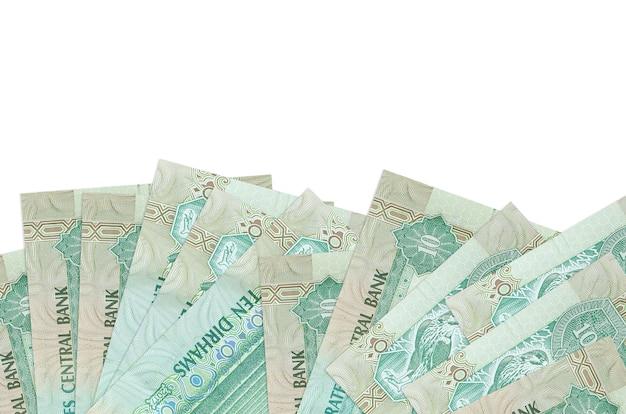 10 uae 디르함 지폐는 복사 공간이있는 흰 벽에 고립 된 화면의 아래쪽에 놓여 있습니다.