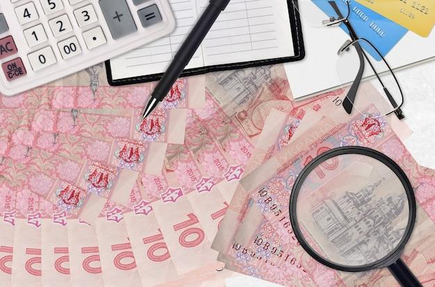 Купюры 10 украинских гривен и калькулятор с очками и ручкой. концепция сезона уплаты налогов или инвестиционные решения. ищу работу с высоким заработком