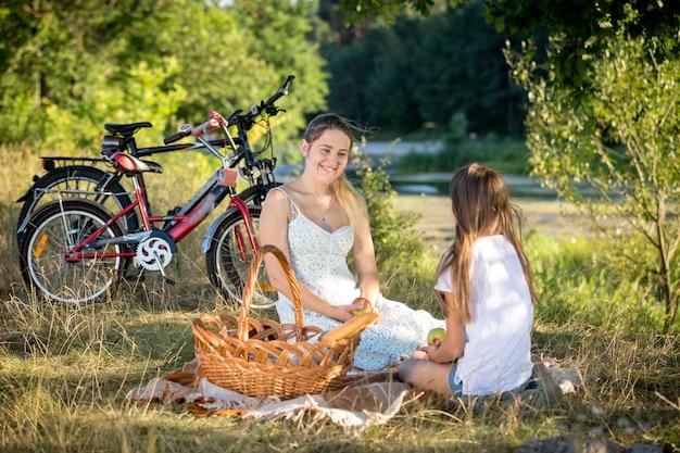 젊은 엄마와 함께 강가에서 피크닉을 즐기는 10세 소녀