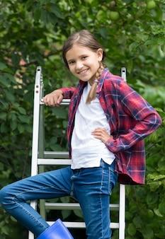 정원의 접사다리에서 포즈를 취하는 10세 소녀