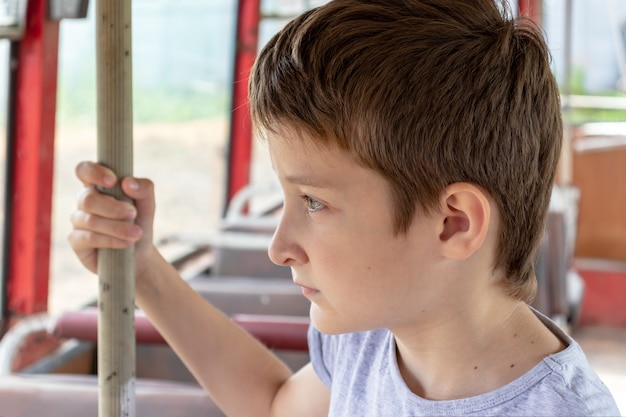 A 10 years boy riding in a old vintage bus, he is sad because his poor life and the bus moving going on a dirty country road