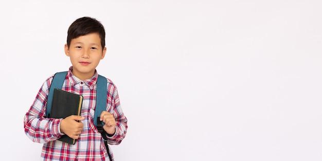 白い表面のバナーコピースペースで隔離のバックパックを持つ10歳の少年
