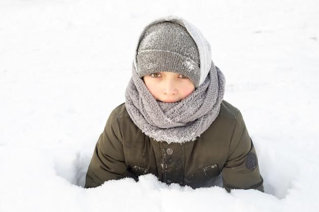 10-летний мальчик в зимнем снегу развлекается в теплой одежде. холодная погода
