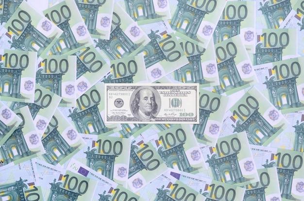 100-долларовая банкнота лежит на множестве зеленых денежных номиналов в 100 евро