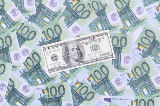 100-долларовая банкнота лежит на множестве зеленых денежных номиналов в 100 евро.