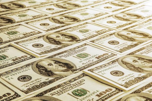 100枚の米国の紙幣の山。 100ドル札、ドル背景画像の現金。