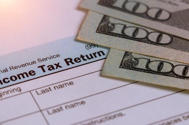 税金100個の請求書を含む米国1040個の確定申告のクローズアップ