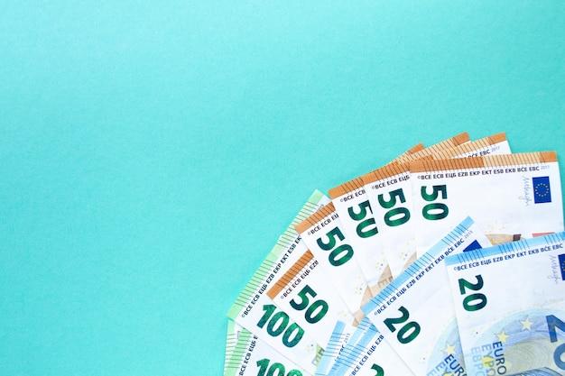 左隅が100、50、20ユーロの紙幣。青色の背景に。お金と金融の概念。テキストのための場所。