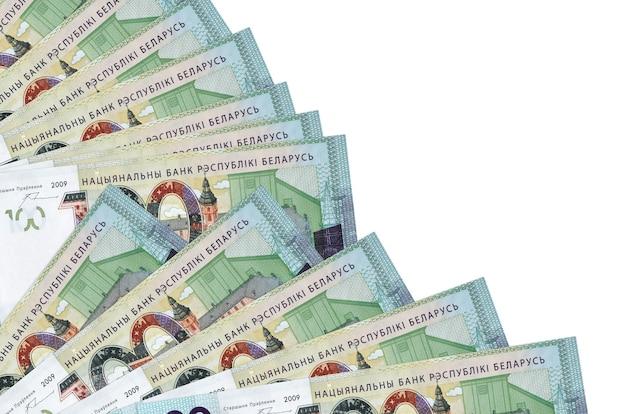 Банкноты 100 белорусских рублей лежат изолированно на белой стене с копией пространства, сложенными в веер крупным планом. понятие времени выплаты жалованья или финансовые операции
