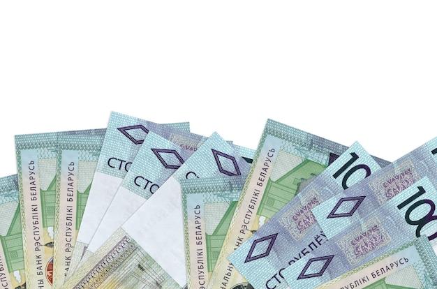 Купюры 100 белорусских рублей лежат на нижней стороне экрана, изолированной на белой стене с копией пространства.