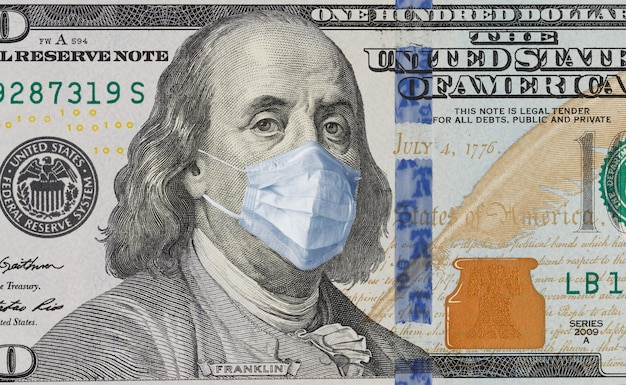 A 100 bill with a medical mask on benjamin franklin from the covid-19