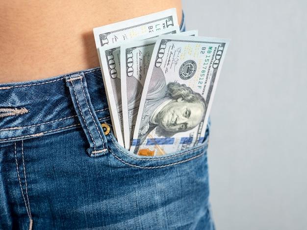 彼のジーンズのフロントポケットから100枚の紙幣が突き出ているポケットの中のお金の概念