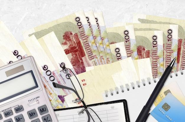 100カンボジアリエルの法案とメガネとペンで電卓。納税の概念または投資ソリューション。財務計画または会計士の事務処理 Premium写真