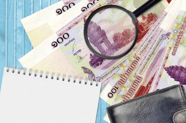 100カンボジアriels手形と拡大鏡と黒い財布とメモ帳