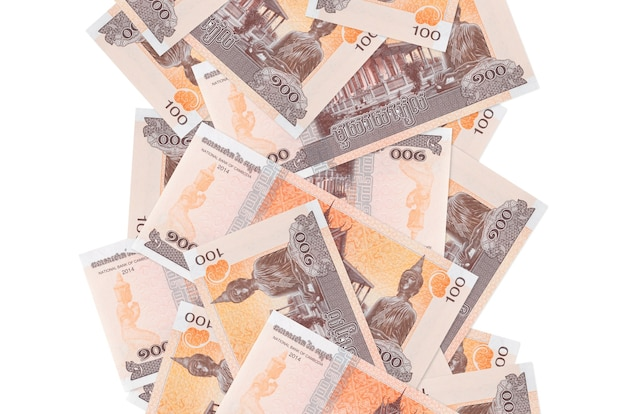 100個のカンボジアリエル紙幣が白で隔離されて飛んでいます。多くの紙幣が左右に白いコピースペースで落ちています Premium写真