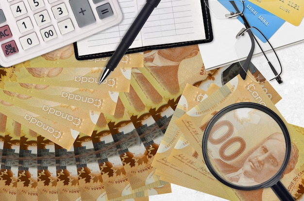 Банкноты 100 канадских долларов и калькулятор с очками и ручкой. концепция сезона уплаты налогов или инвестиционные решения.