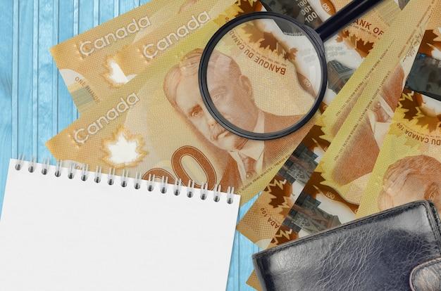 Банкноты 100 канадских долларов и увеличительное стекло с черным кошельком и блокнотом. понятие о поддельных деньгах. поиск различий в деталях денежных купюр для обнаружения фальшивых денег
