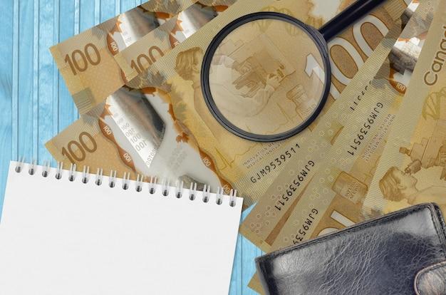 100 캐나다 달러 지폐와 검은 색 지갑과 메모장이있는 돋보기
