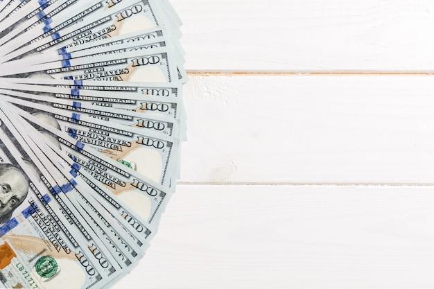 100ドル通貨ファンをクローズアップ、copyspaceと色付きの背景にビジネスのトップビュー