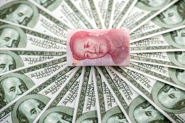 Банкноты 100 долларов с банкнотой в сто юаней, ренминби.