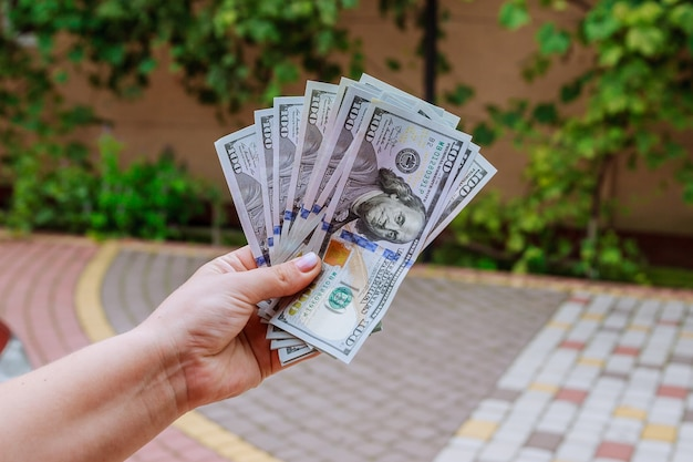 100 - 여자의 손에 든 달러 지폐. 계산하거나 돈을 쓰십시오.