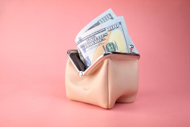 100 долларов наличными в коже на розовом пространстве.
