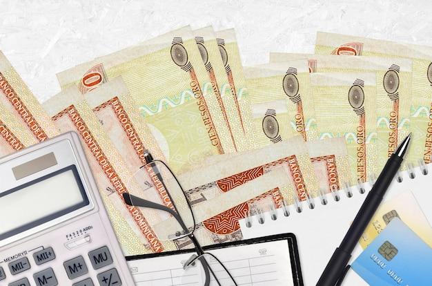 100ドミニカペソの請求書とメガネとペン付きの電卓。納税シーズンのコンセプトまたは投資ソリューション。フィナンシャルプランニングまたは会計士の事務処理