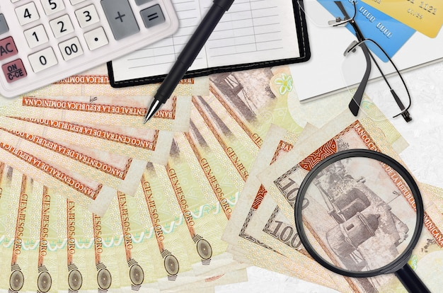 100 доминиканских песо и калькулятор с очками и ручкой. концепция сезона уплаты налогов или инвестиционные решения. ищу работу с высокой зарплатой