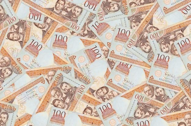 100枚のドミニカペソ紙幣が山積みになっています。豊かな生活の概念的な背景。巨額