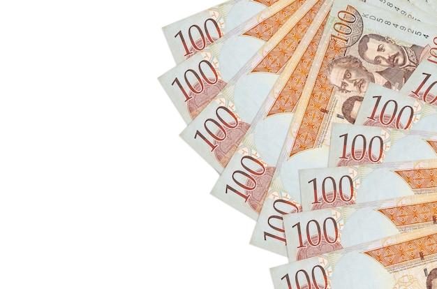 100ドミニカペソ紙幣はコピースペースで白い背景に分離されて横たわっています