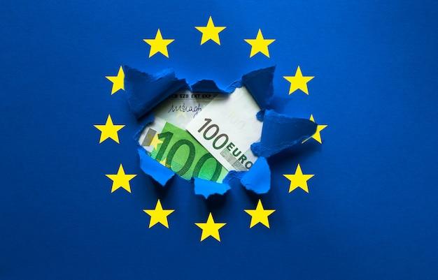 Банкнота достоинством 100 евро выходит из рваной бумаги с символом европы